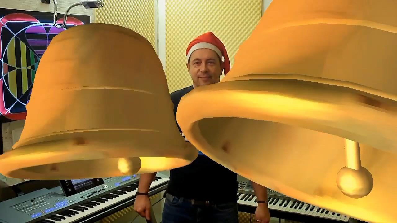 Niño steht zwischen 2 goldenen Weihnachts-Glocken